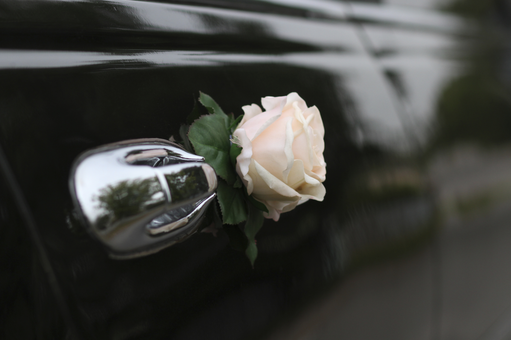Decorative flower on the door of black wedding limo
